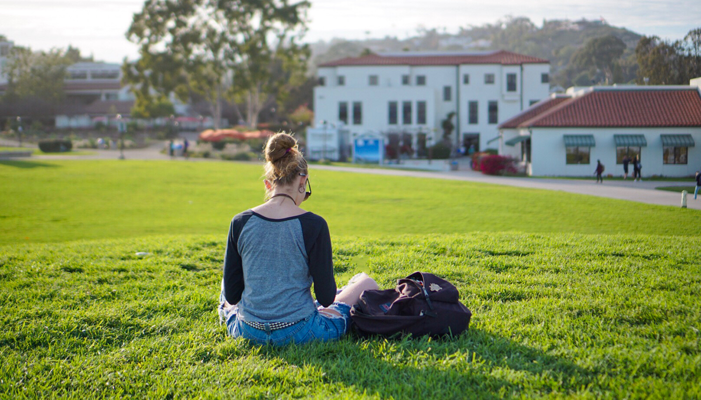 SBCC student sitting on the west campus lawn studying.